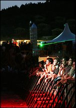 [The H2000 audience enjoy the music on a barmy evening on the beach.]
